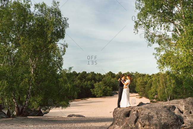 View at distance of couple in wedding gowns standing on rock and embracing happily against green trees and blue sky