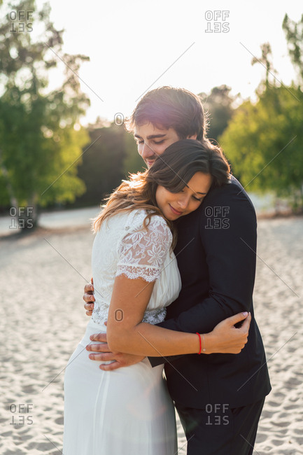 Loving man embracing beautiful bride in elegant dress and looking at each other while standing on sandy coast in sunlight