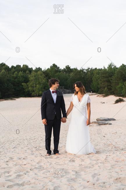 walking wedding couple on picturesque coastline