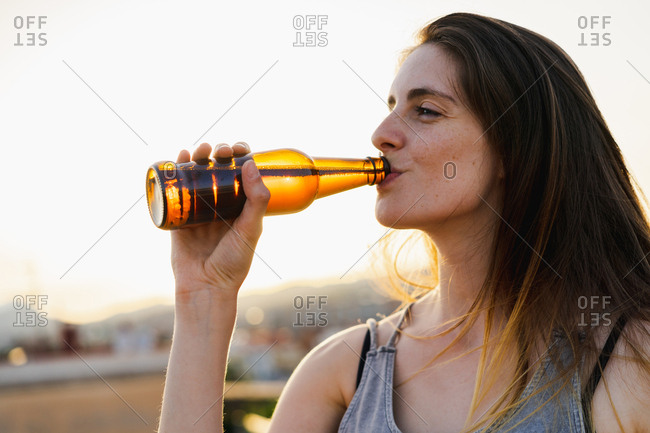 Happy woman holding brown glass bottle
