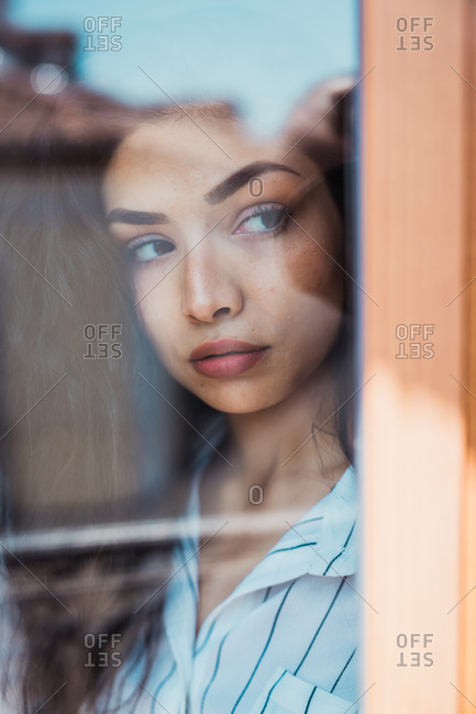 Shot through glass of young serious brunette with long hair wearing shirt and looking pensively away
