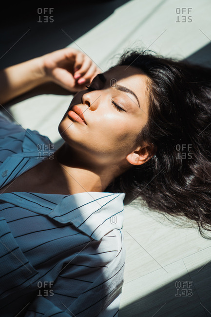 Beautiful brunette lying on floor in sunlight