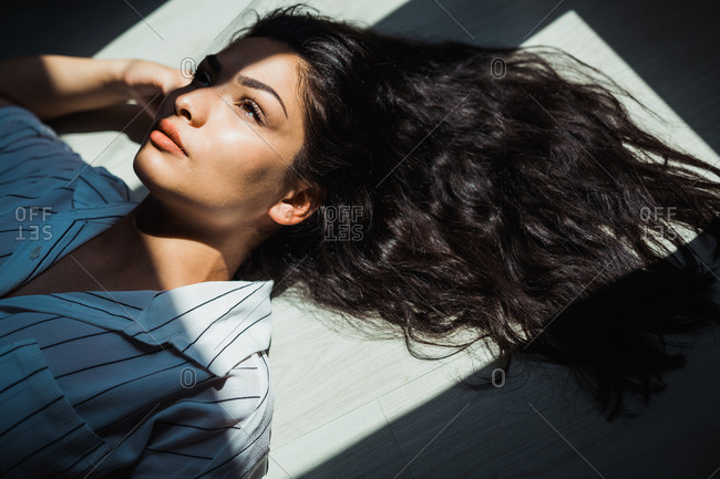 From above of young provocative woman with long black hair lying spread on floor in shadow and sunlight