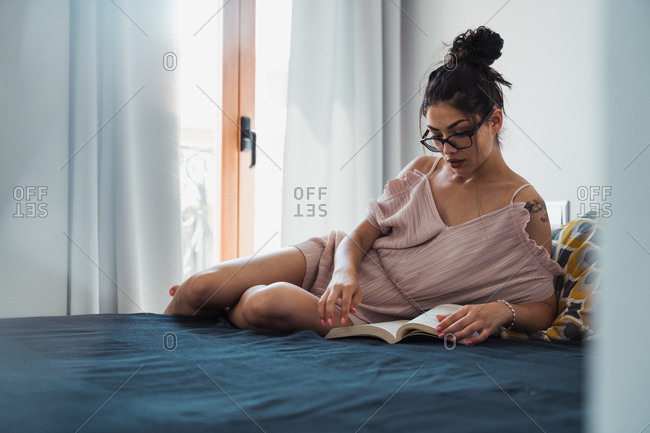 Woman with book chilling on bed