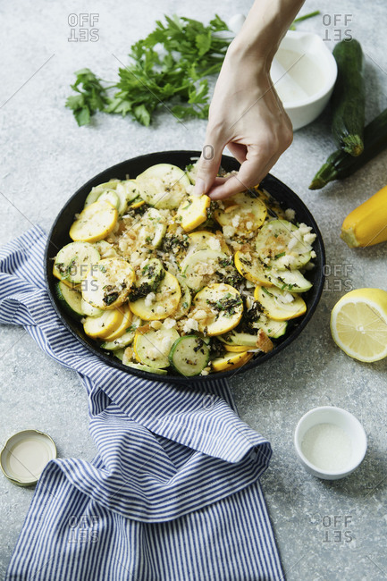 Female hands arranging squash slices, cooking squash and zucchini gratin with herb salsa, cheese and breadcrumbs