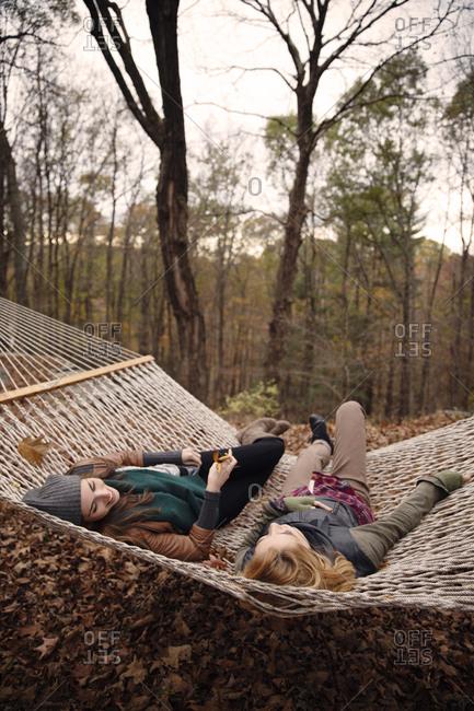 Two women laying in hammock in fall