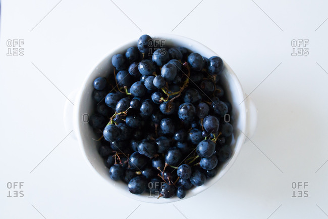 Black grapes in white bowl