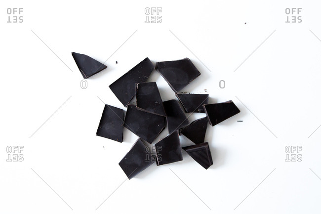 Black chocolate pieces on white surface
