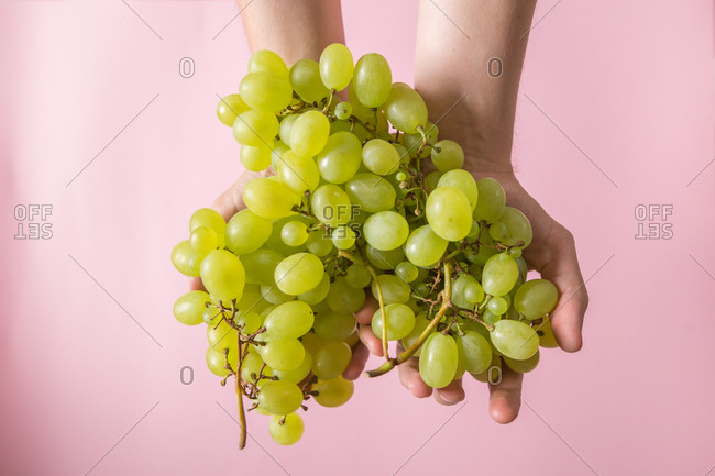 Man holding grapes with pink background