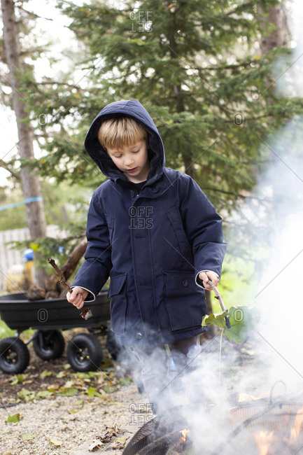 Young blonde boy burns leaves in a firepit in a backyard