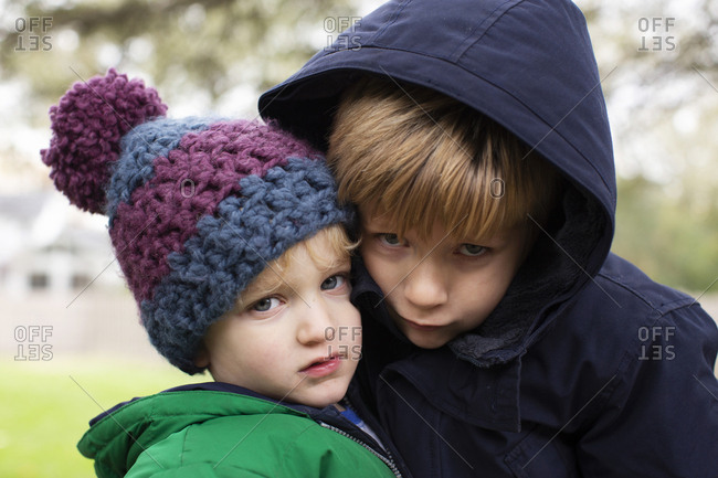 Portrait of two young brothers together outside in winter