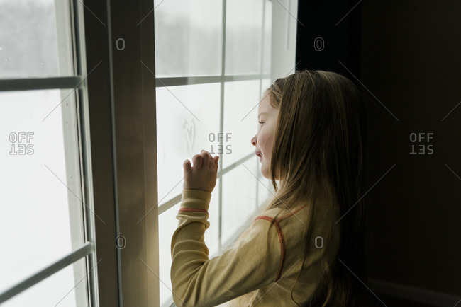 Smiling girl draws a heart with her finger on a fogged up window.