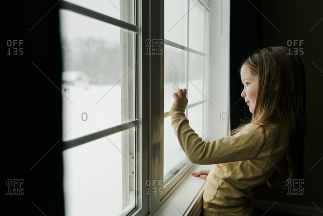 Smiling young girl draws on fogged up window with finger.