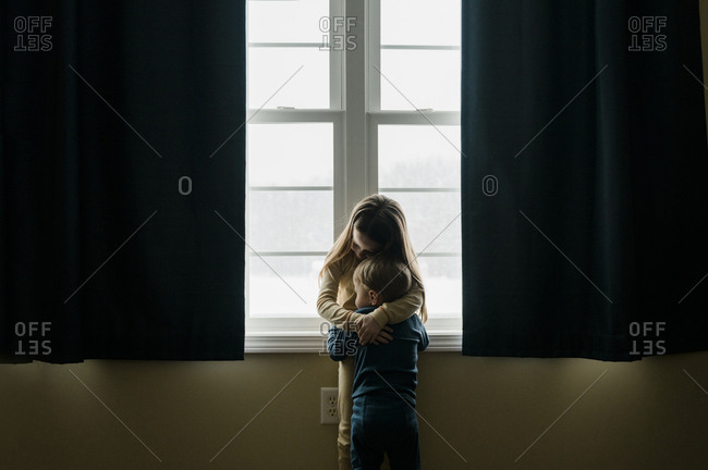 Young siblings in pajamas hug in front of large window