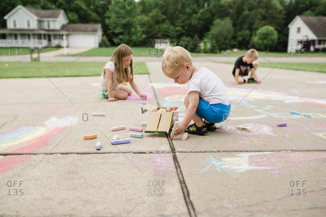 Baby and siblings draw on driveway with chalk