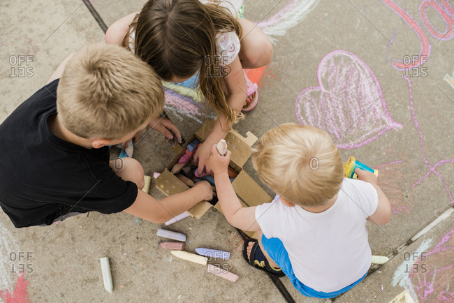 Above view  of siblings reaching into box for chalk