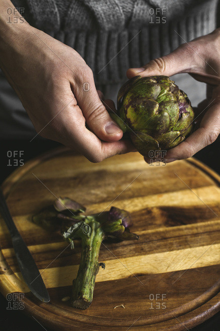 A man prepares lunch with artichokes