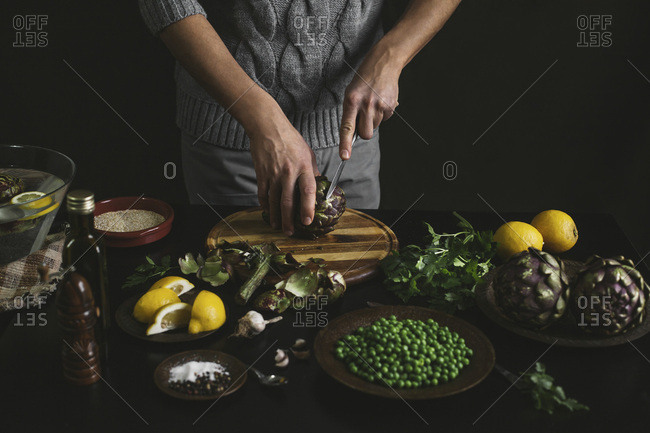 A man prepares lunch with artichokes and peas