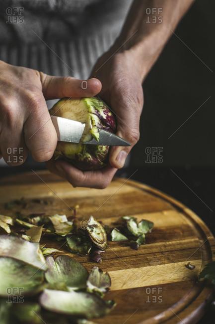 A man preparing an artichoke