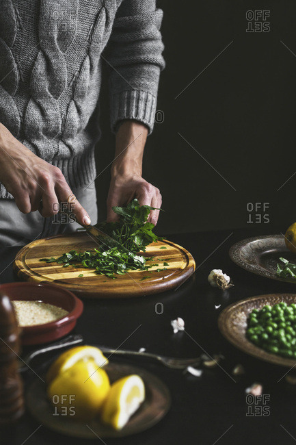 A mans hands chopping parsley while preparing a meal