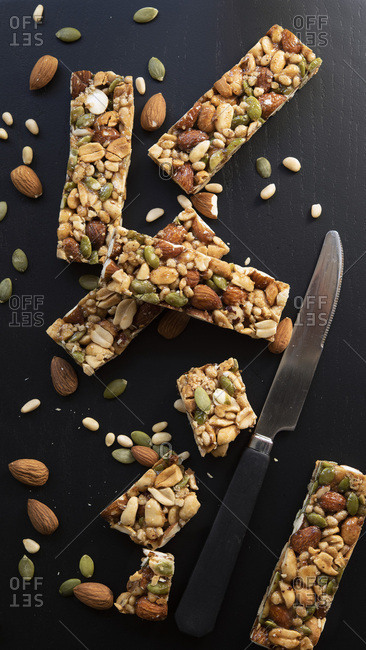 Nut and Seed Bars with a knife on a black background.