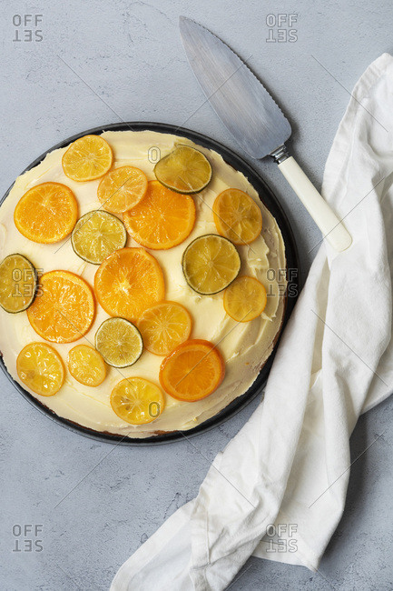 A round homemade orange cake with a cake server.