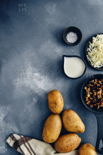 Ingredients for cheesy mashed potatoes on a dark background photographed from top view. Roasted walnuts in a cast iron pan, grated cheese on a black ceramic plate, milk in a black ceramic cup and sea salt in a black ceramic bowl accompany.