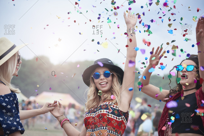 Friends dancing among confetti at the music festival