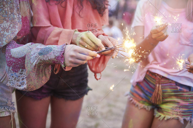 Women having fun with sparklers at music festival