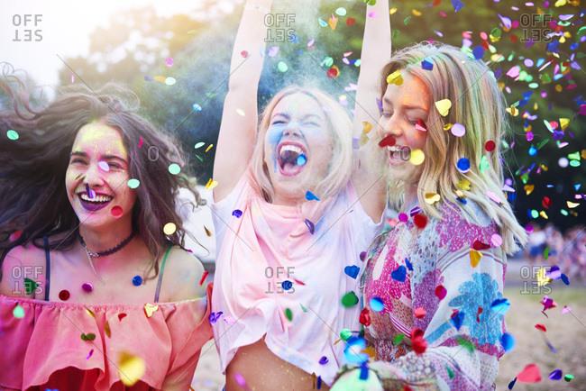 Friends having fun with holi powder and confetti