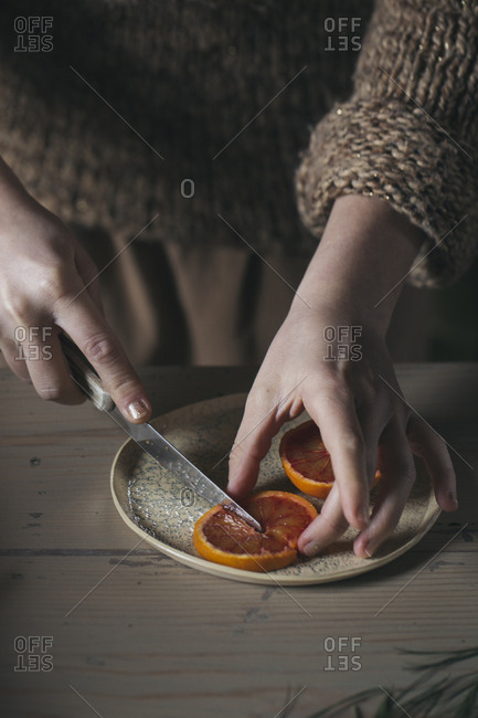 Woman's hands cutting slice of blood orange