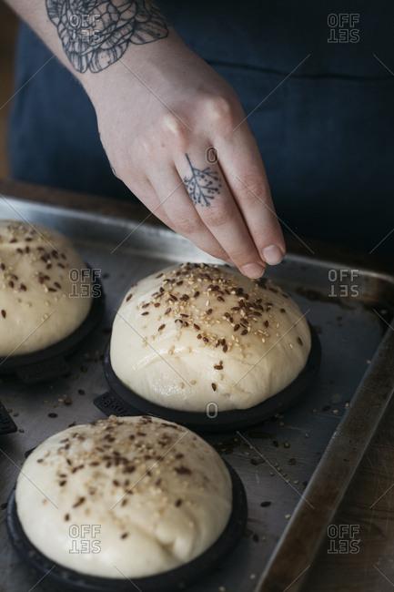 Woman sprinkling seeds on vegan burger rolls
