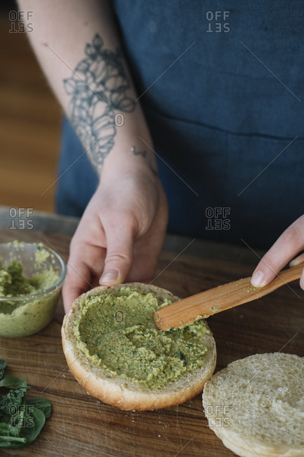 Woman preparing vegan burger, spreading avocado cream on bread roll