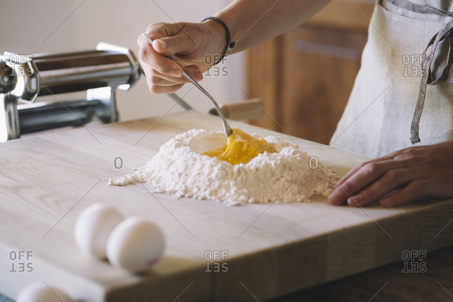 Woman preparing pasta dough, flour and eggs