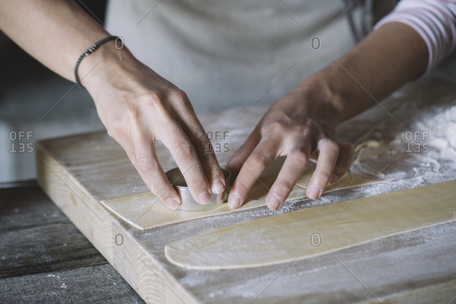 Woman preparing ravioli, pasta dough cutting out on pastry board