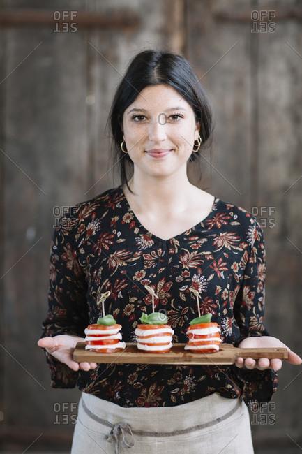 Portrait of smiling woman serving Caprese Salad