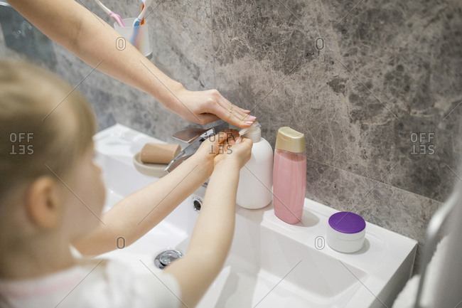 Mother helping daughter washing hands