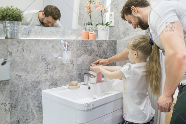 Father helping his little daughter washing her hands