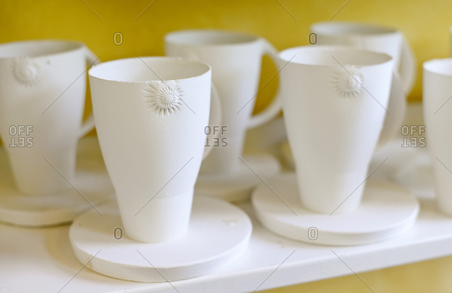 Mugs on shelf in porcelain workshop