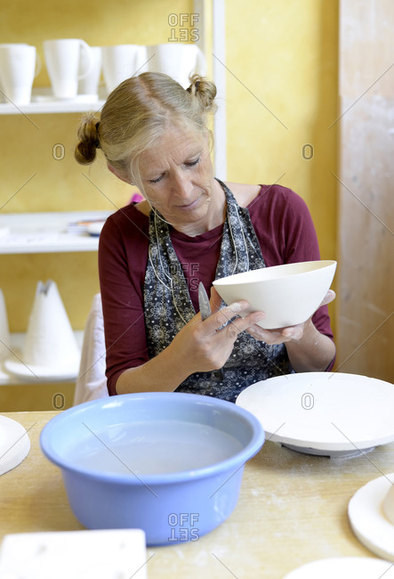 Woman working on bowl in porcelain workshop