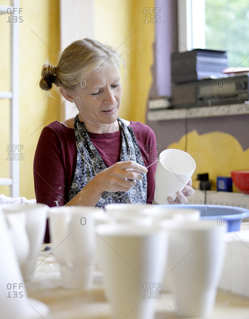 Woman working on mug in porcelain workshop