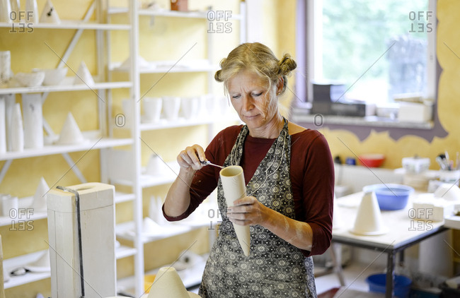 Woman working on product in porcelain workshop