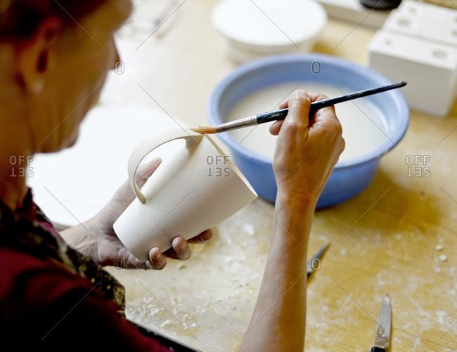 Woman using brush on mug in porcelain workshop