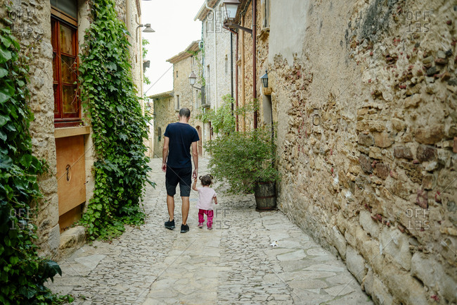 Spain, Catalonia, Peratallada, Medieval Town, Father and daughter walking hand in hand, rear view