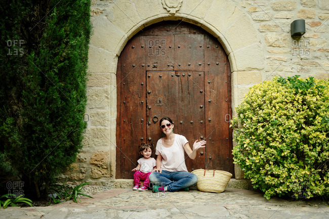 Mother and baby girl sitting at old wooden door