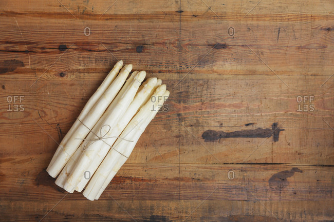 Bunch of white asparagus on wood, copy space