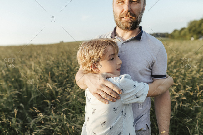 Father and son standing on a meadow hugging each other