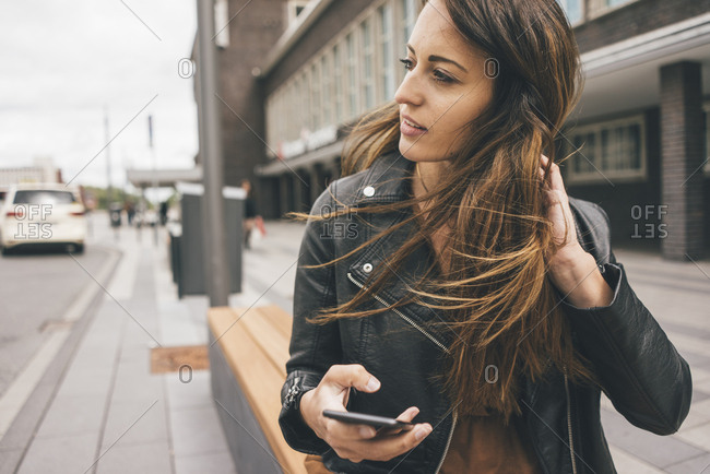 Young woman with windswept hair holding cell phone in the city