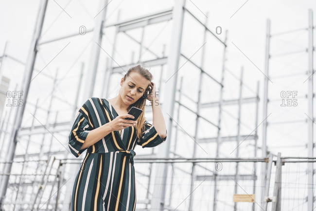 Young woman using cell phone at scaffolding