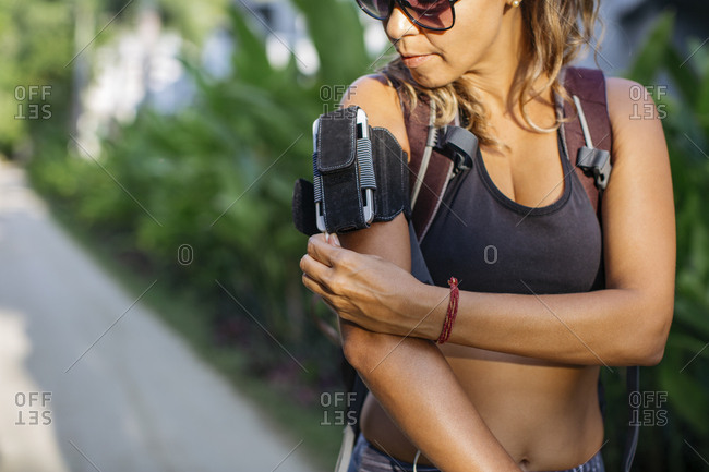 Thailand, Koh Phangan, Sportive woman wearing cell phone case at upper arm